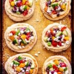 Six mini Greek Pita Pizzas on a sheet pan.