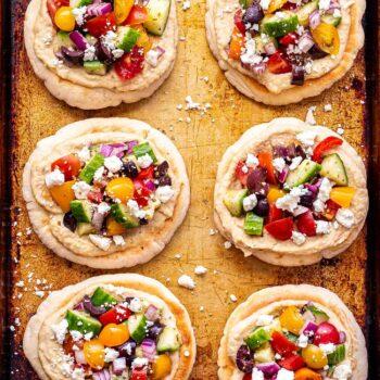 Six mini Greek Pita Pizzas on a sheet pan.