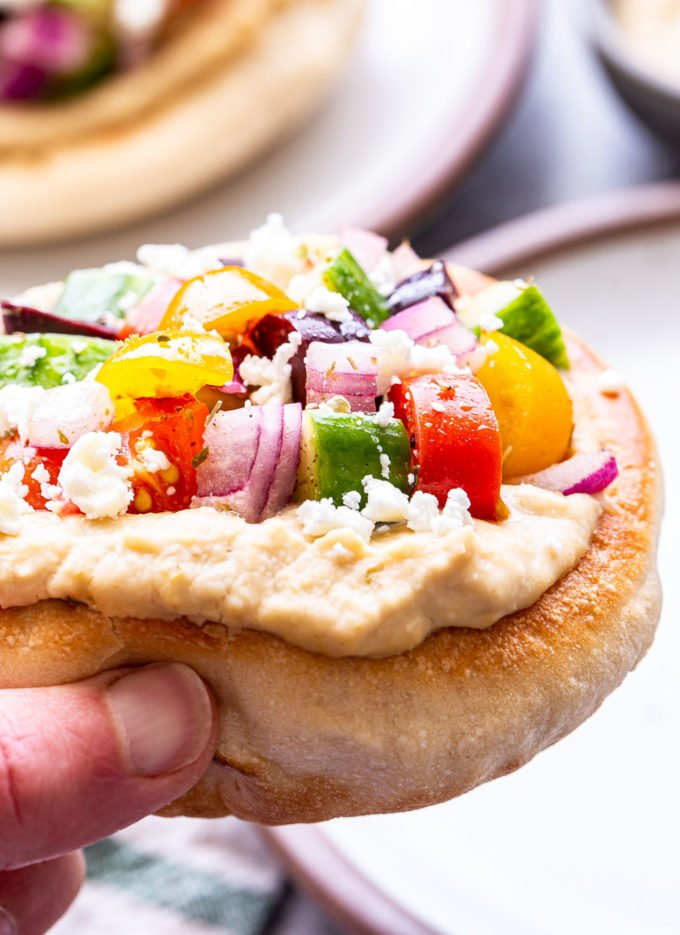 Hand holding a Greek pita pizza topped with hummus, cucumbers, tomatoes, onion and olives