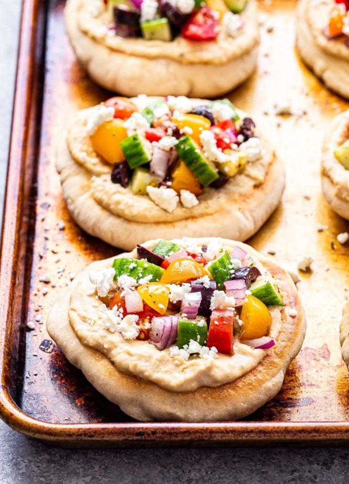 Greek Pita Pizzas on a sheet pan topped with Greek salad.