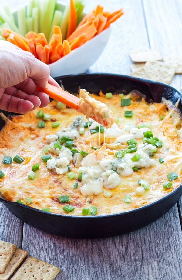 Hand holding a carrot stick that's been dipped into a cast iron skillet filled with buffalo chicken dip that's topped with melted cheese, blue cheese grumbles and slices of green onion.