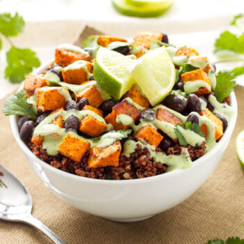 Sweet Potato and Black Bean Quinoa Bowl in white bowl topped with avocado drizzle and lime wedges.