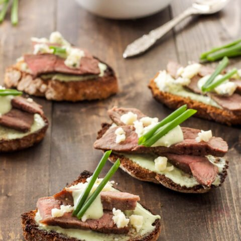 Steak Crostini with Blue Cheese Sauce | Crostini topped with a creamy blue cheese sauce and juicy slices of steak!