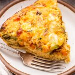 A slice of Crustless Vegetable Quiche on a white plate with a fork.
