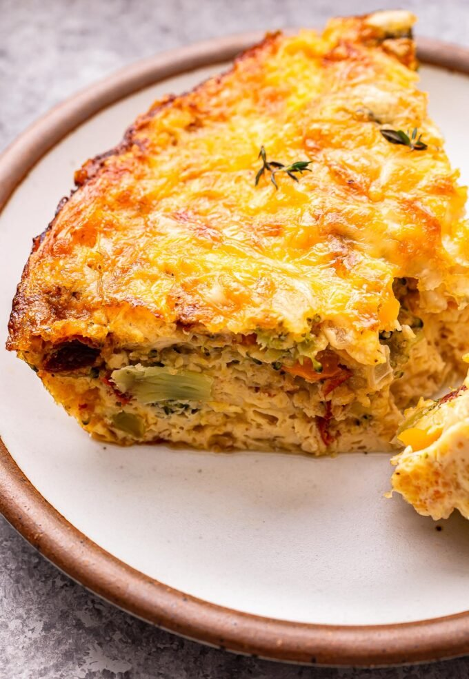 Slice of Crustless Vegetable Quiche on a white plate.