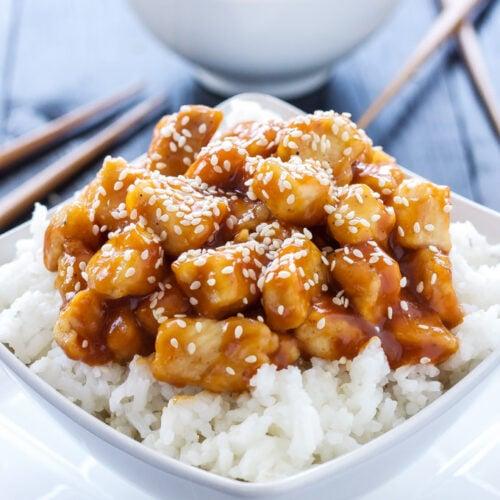 Honey Sriracha Sesame Chicken in a white bowl over rice.