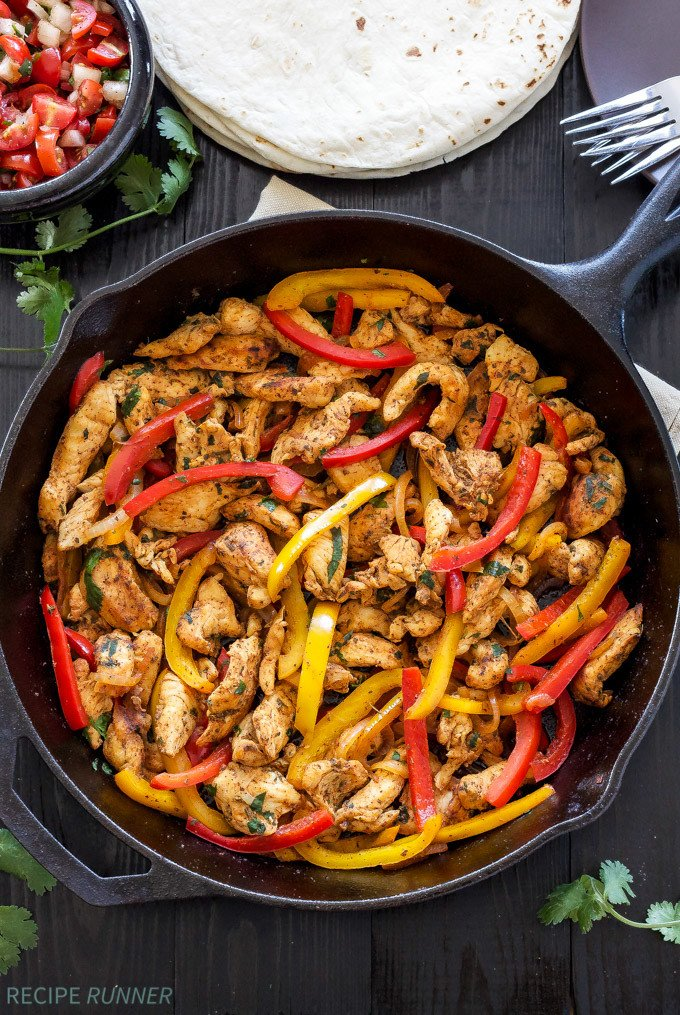 Skillet chicken fajitas with red and yellow peppers in a black cast iron skillet.