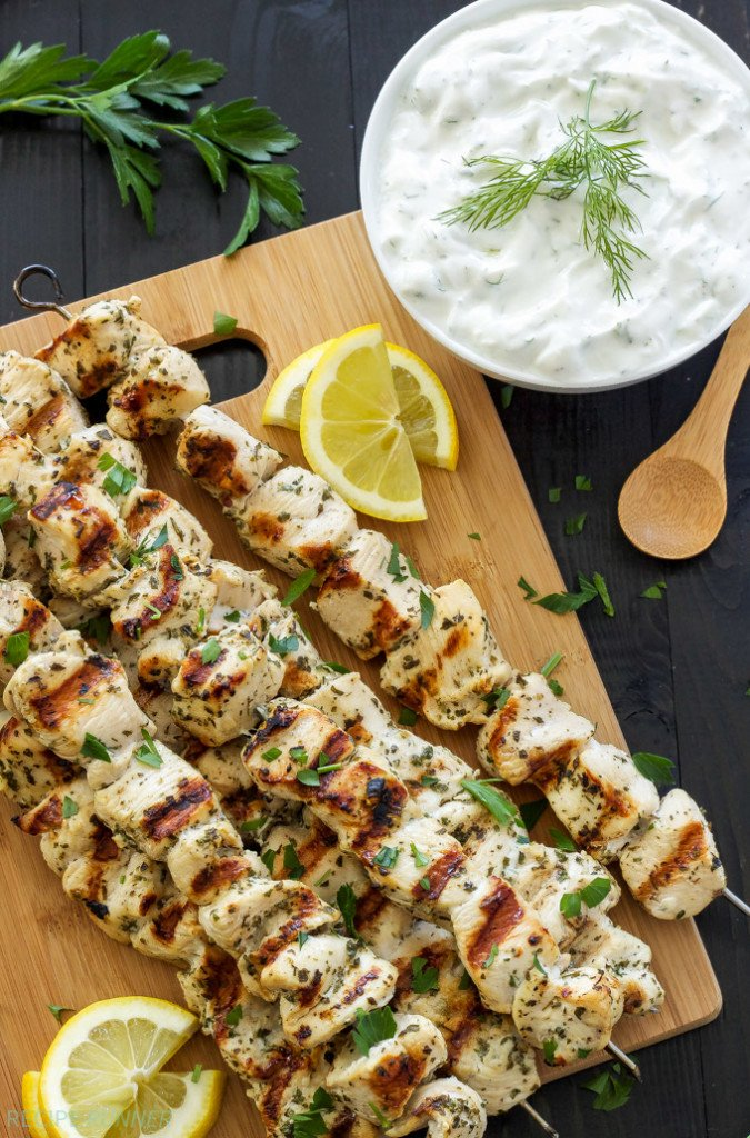 Greek Lemon Chicken Skewers on cutting board with a small white bowl of tzatziki.