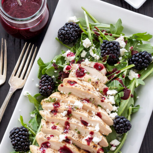 Grilled Chicken and Goat Cheese Salad with Blackberry Vinaigrette on rectangular white plate