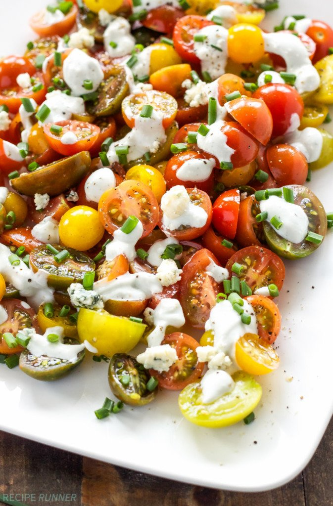 Heirloom Tomato and Blue Cheese Salad on white serving plate drizzled with blue cheese dressing.