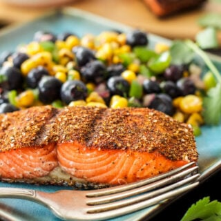 Southwest Grilled Salmon with Blueberry Corn Salsa on the side. On a blue plate with a fork.