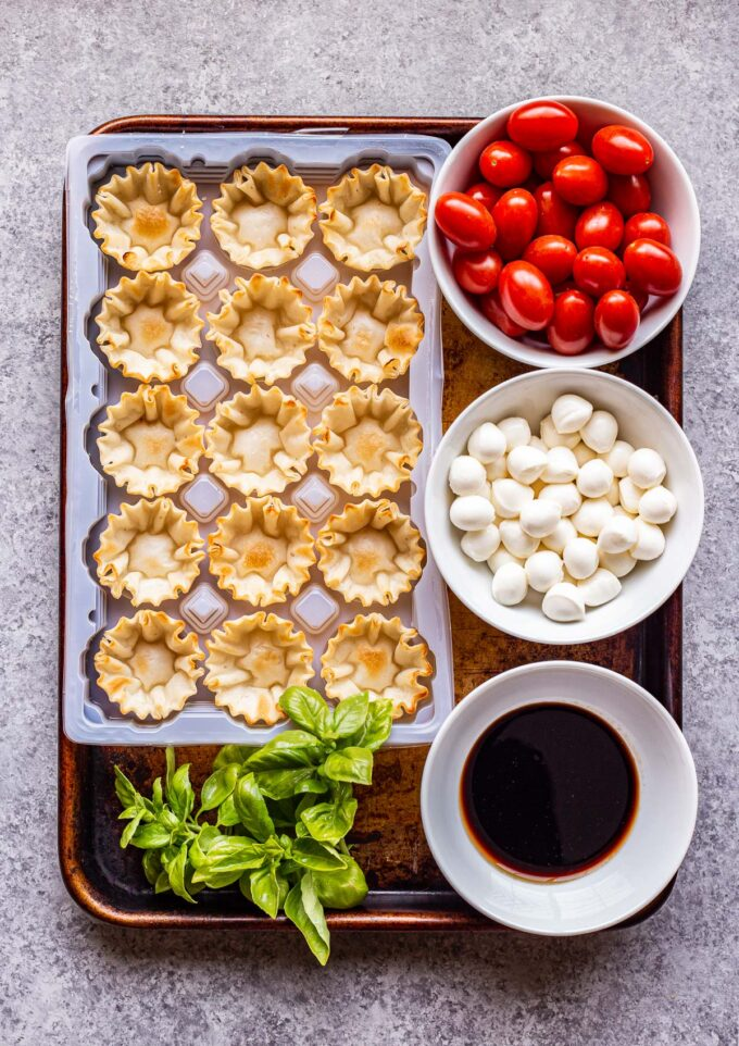 ingredients used to make Mini Caprese Cups on a sheet pan.