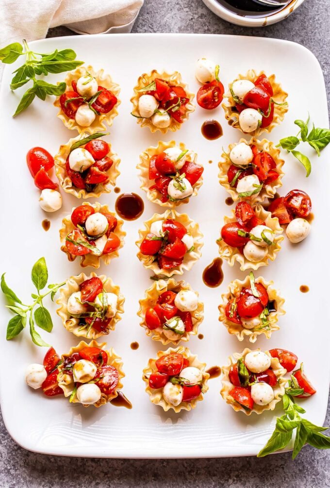 white plate with 15 Mini Caprese phyllo Cups on it. Basil leaves are garnished on the plate.