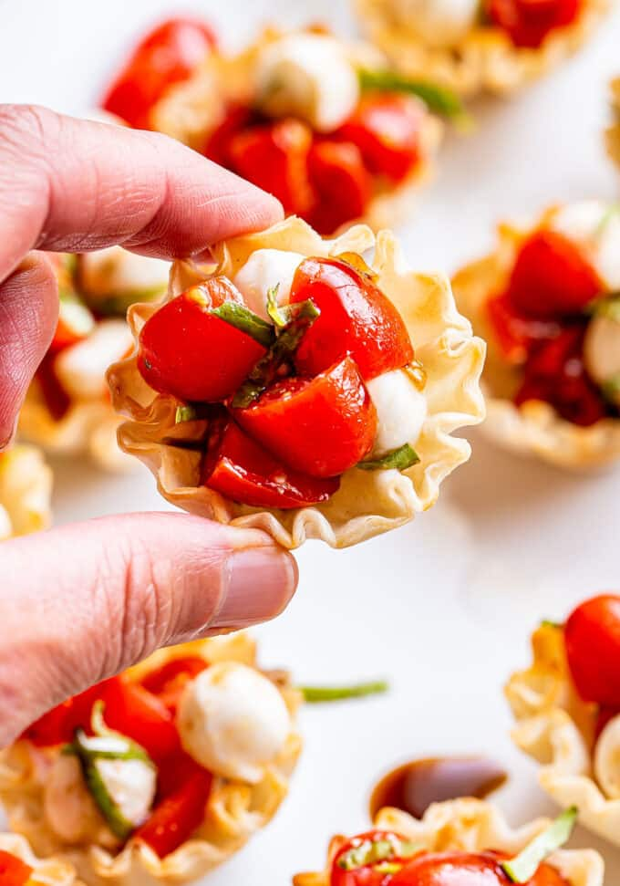 Hand holding one of the Mini Caprese Cups