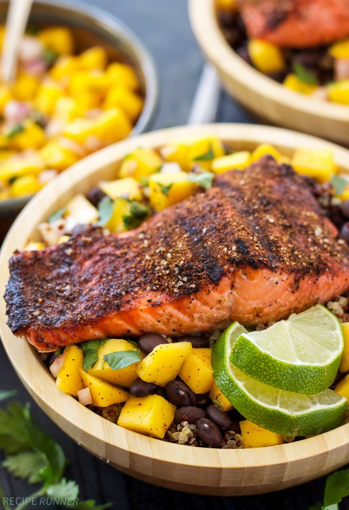 Caribbean Salmon Quinoa Bowls topped with mango salsa, black beans and lime wedges