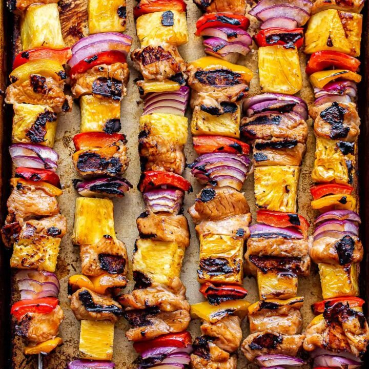Overhead photo of six Hawaiian chicken, pineapple, red bell pepper and red onion chicken skewers on a sheet pan.