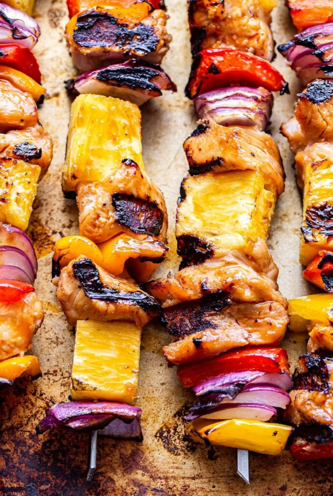 Four Hawaiian chicken, pineapple, red bell pepper and red onion chicken skewers on a sheet pan.
