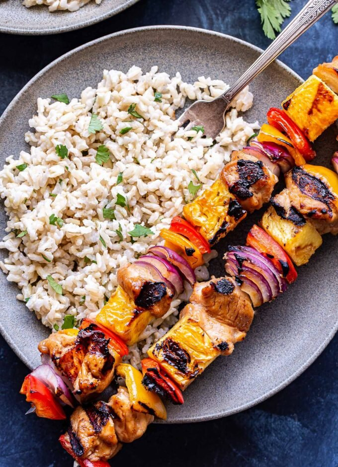 Overhead photo of Two chicken skewers threaded with pineapple, red bell peppers and red onions on a gray plate with cilantro rice.