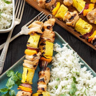 Hawaiian Chicken Skewers with Cilantro Coconut Rice on the side. on square blue plate with