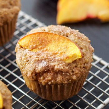 Peach Quinoa Muffins topped with peach slice on a wire cooling rack.