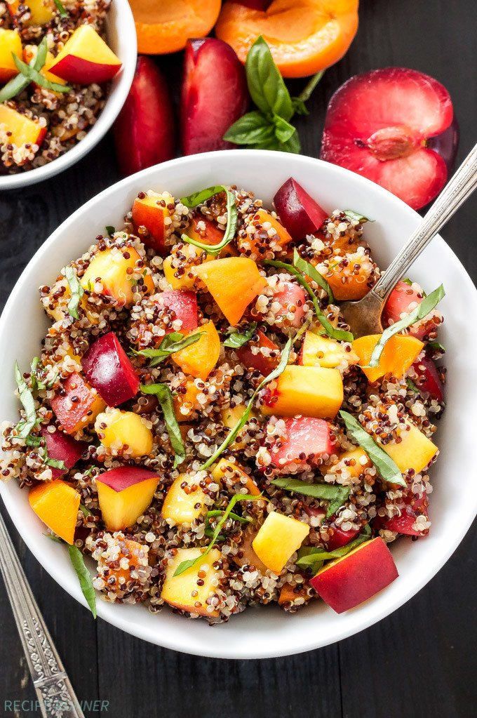 Stone Fruit Quinoa Salad in white serving bowl with spoon. Plums and apricot on the side.