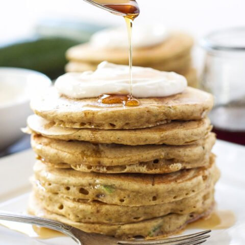 A stack of Zucchini Bread Pancakes topped with Maple Cream Cheese and syrup being spooned over them.