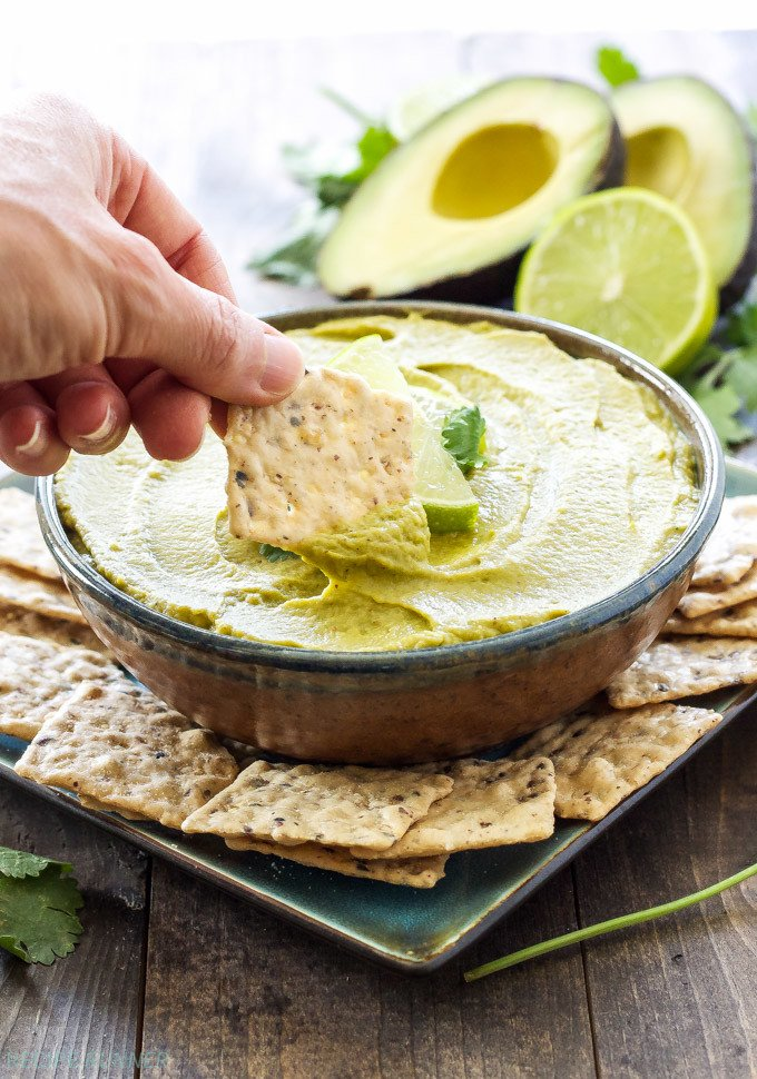 Avocado Lime Hummus in a bowl with a cracker being dipped into it.