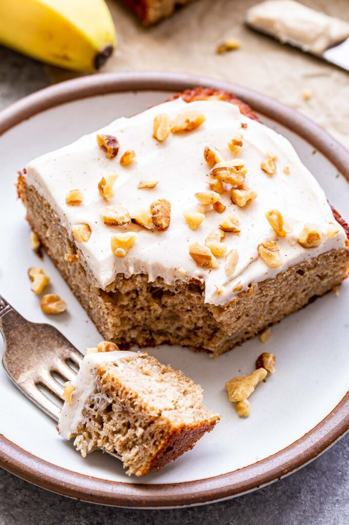 A square slice of the Banana Snack Cake with Cinnamon Cream Cheese Frosting topped with chopped walnuts on a white round plate. A piece is cut out of the slice and on a fork.