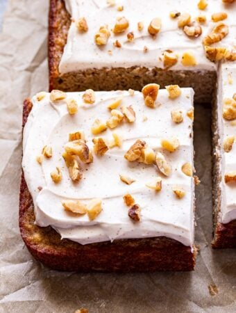 Square edge piece of the Banana Snack Cake with Cinnamon Cream Cheese Frosting topped with chopped walnuts.