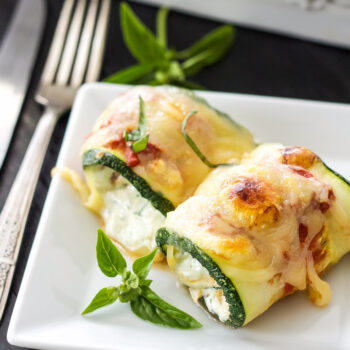 Two zucchini lasagna rolls on a square white plate with silverware next to the plate and a white casserole dish full of the zucchini lasagna rolls behind it.
