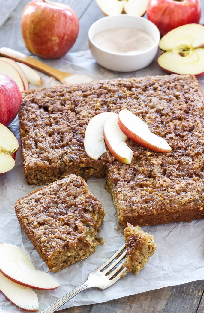 Cinnamon apple snack cake on parchment paper with a square slice cut out. Halved apples in the background.