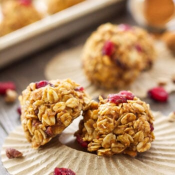 Healthy No Bake Pumpkin Oatmeal Cookies with dried cranberries and pecans on parchment paper.