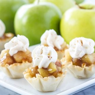 No Bake Apple Pie Bites in mini phyllo cups topped with whipped cream on a white plate. Green apples behind the plate.