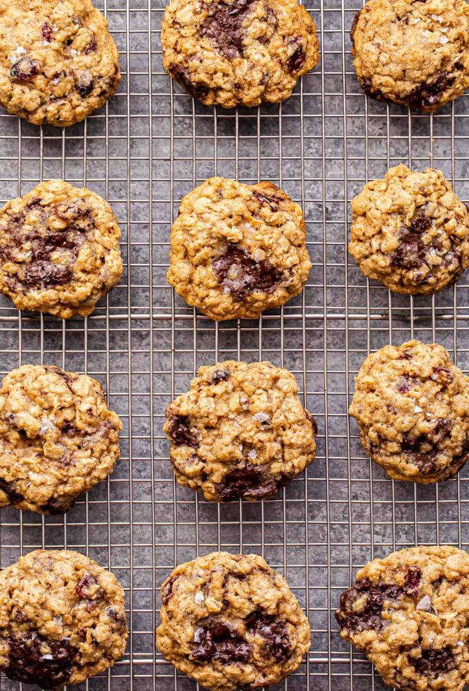 Twelve Oatmeal Dark Chocolate Cranberry Cookies on a wire cooling rack.