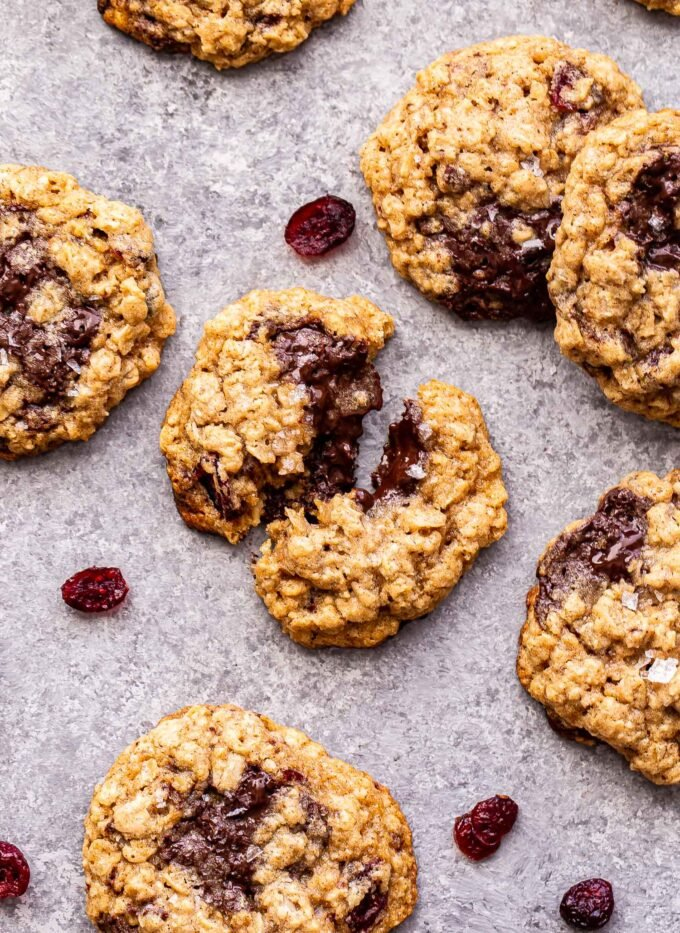 Oatmeal Dark Chocolate Cranberry Cookies on a countertop with dried cranberries scattered around them.