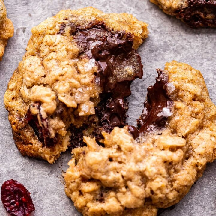Closeup photo of an Oatmeal Dark Chocolate Cranberry Cookie broken in half.