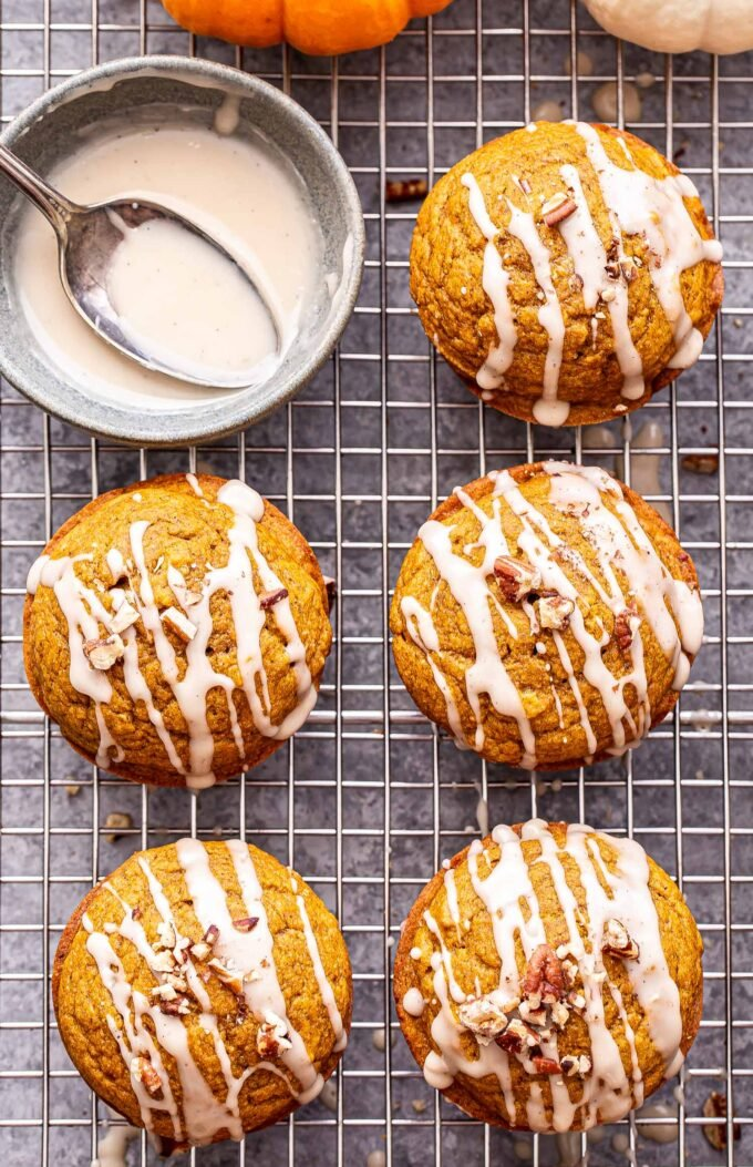 Overhead photo of five pumpkin pecan muffins drizzled with bourbon maple glaze and topped with chopped pecans. A bowl of the glaze with a spoon in it is in the top left corner.