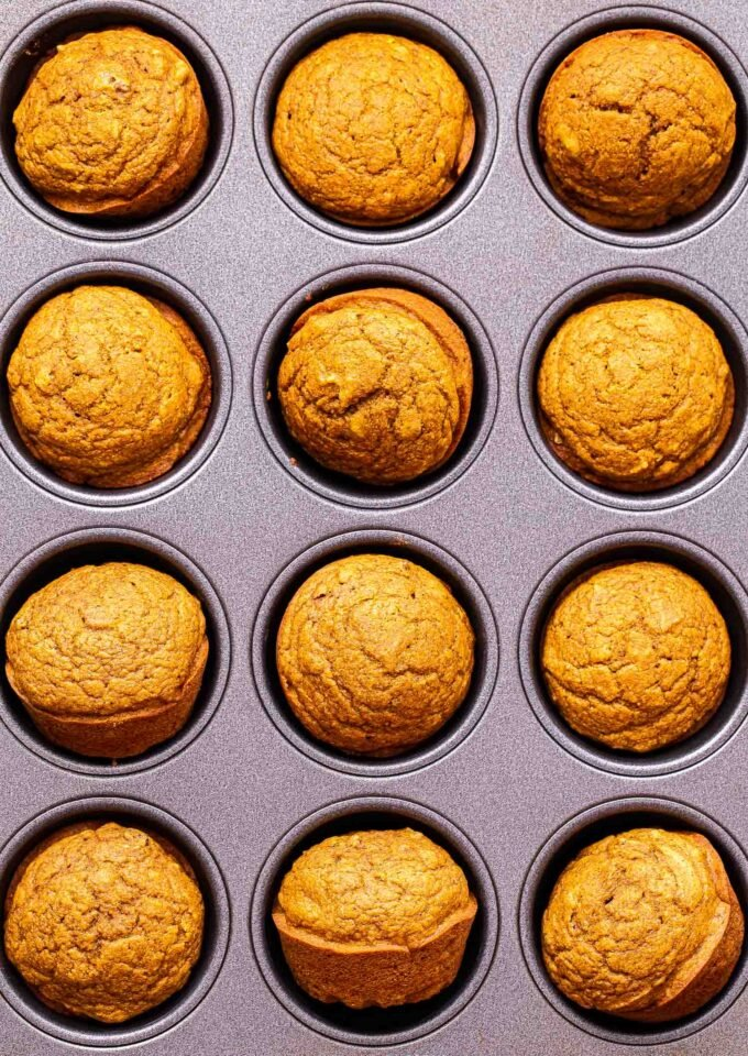 Twelve Pumpkin Pecan Muffins in a muffin pan.