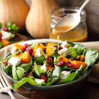 Spoon drizzling cider vinaigrette on top of a bowl of Roasted Butternut Squash Salad.