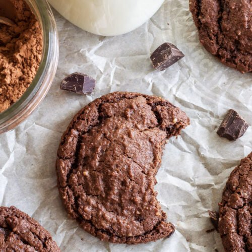 Chewy Chocolate Almond Cookies on parchment paper. One has a bite taken out of it.