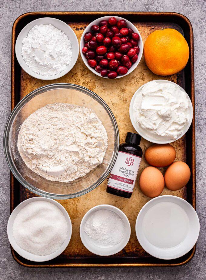Ingredients used to make the cranberry orange yogurt cake on a sheet pan.