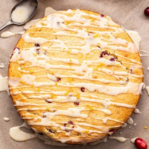 Overhead photo of Cranberry Orange Yogurt Cake on parchment paper with cranberries scattered around it and a jar of the glaze behind it.