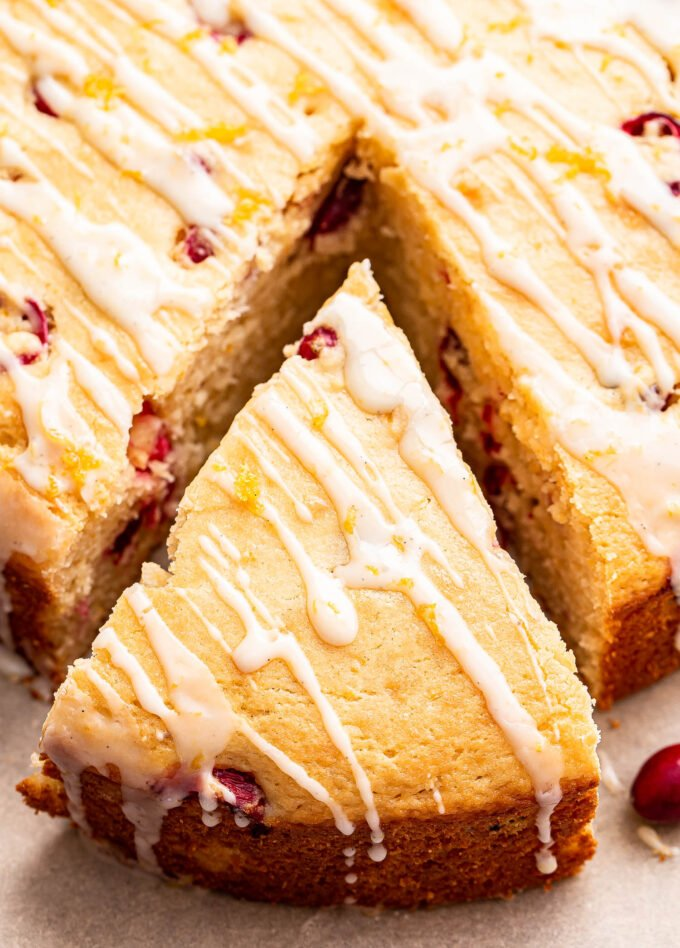 Cranberry Orange Yogurt Cake with glaze drizzled on top and a slice cut from the cake.