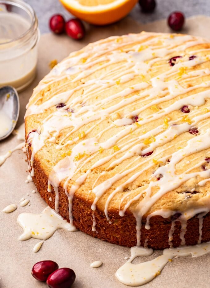 Cranberry Orange Yogurt Cake with glaze drizzled over the top. Cake is on parchment paper.