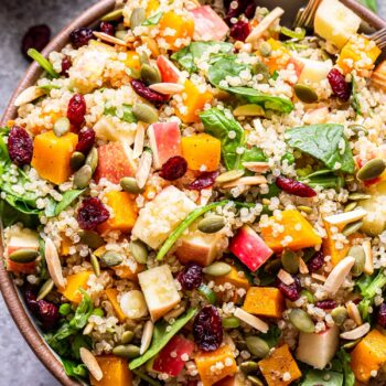 Harvest quinoa salad with butternut squash, apples, dried cranberries, pepitas, spinach, and toasted almonds in a white serving bowl with spoons in it. A jar of cider vinaigrette behind the bowl.