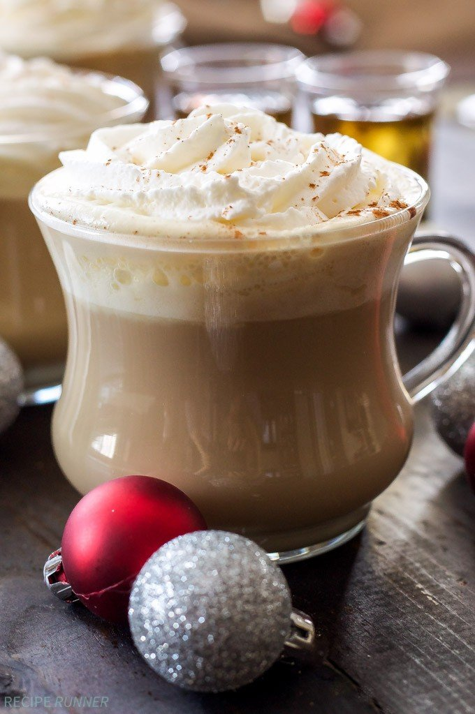 Bourbon eggnog latte topped with whipped cream. A couple of Christmas ornaments are in front of the glass.