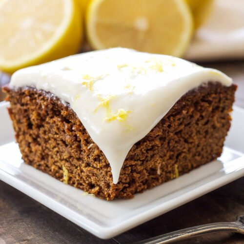 A slice of Gingerbread Cake with Cream Cheese Frosting on a white plate with lemons behind it.