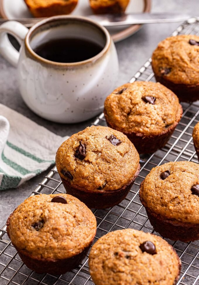 Gingerbread Chocolate Chip Muffins on a wire rack with a cup of coffee to the side of them.