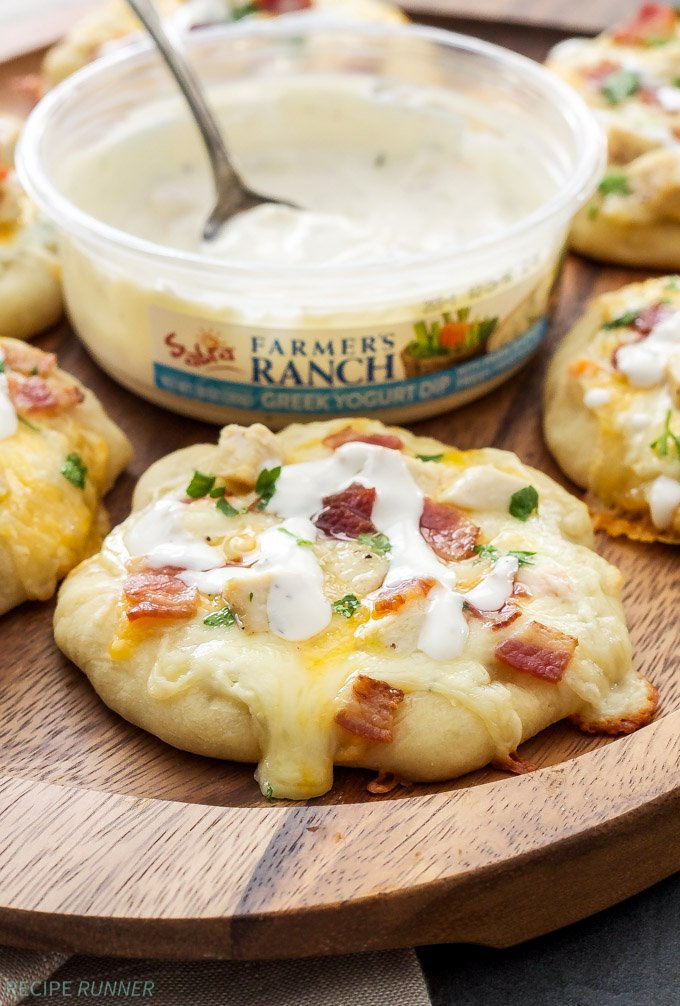 Chicken Bacon Ranch Mini Pizzas | Mini pizzas topped with ranch Greek yogurt dip, lots of cheese, chicken and of course bacon! Perfect for dinner or a game day appetizer!