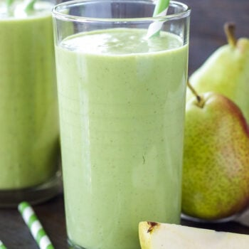 Two pear ginger smoothies in tall glasses with green and white striped straws in them. Whole pears in the background and slices next to them.